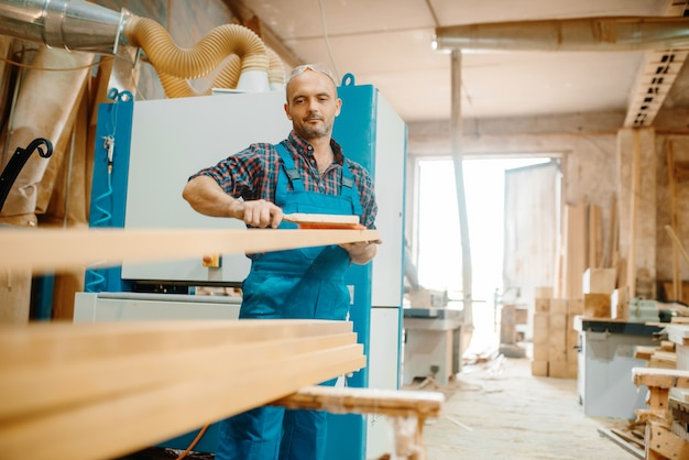 Carpenter processes board on plane machine, woodworking, lumber industry, carpentry.