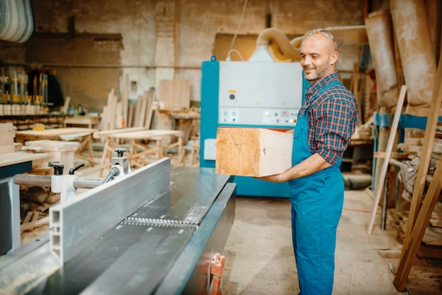 Carpenter processes wooden beam on plane machine, woodworking, lumber industry, carpentry.