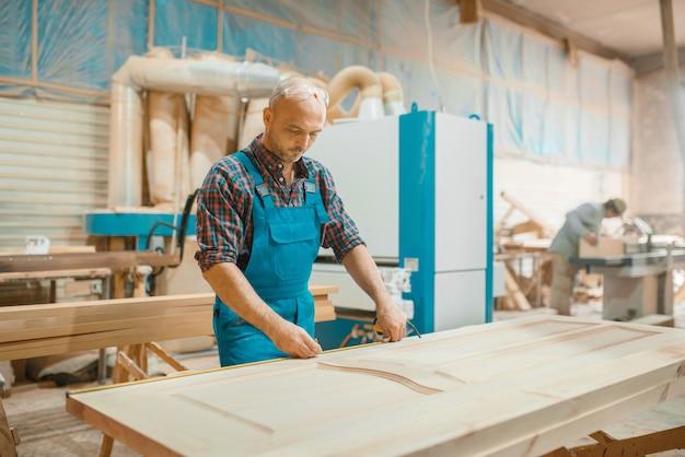 Carpenter processes wooden door, woodworking, lumber industry, carpentry.