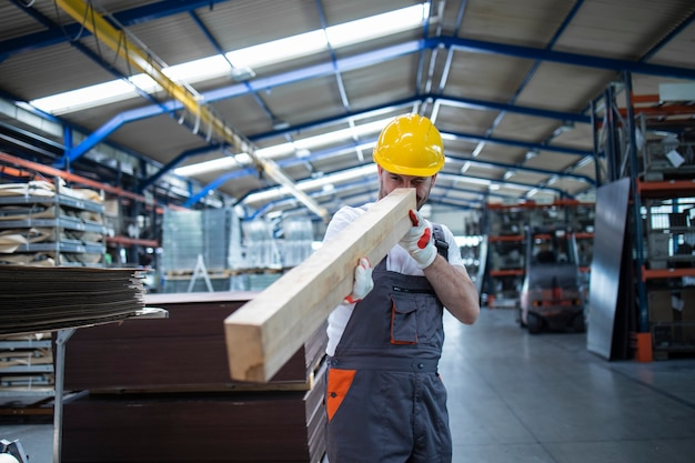 Carpenter production line worker checking wood material for furniture production in factory hall