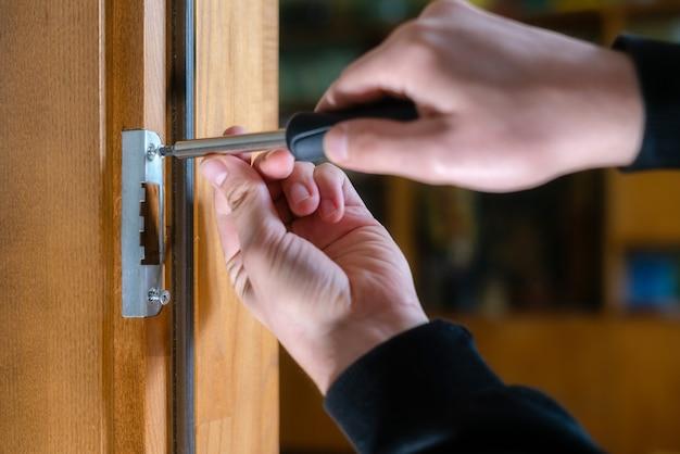 大工がドアロックを修理し、便利屋がドアのヒンジを締めます。