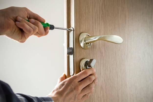 Carpenter repairs door lock. installation of the door handle with a tool.