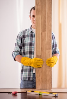 Carpenter in rubber gloves holding wooden planks.