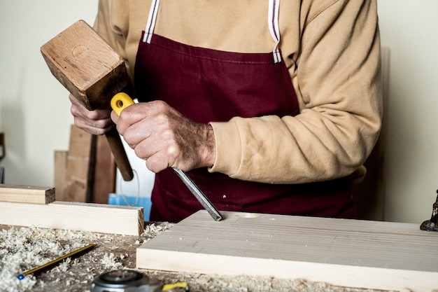 Carpenter's hands with chisel on the woodworking bench