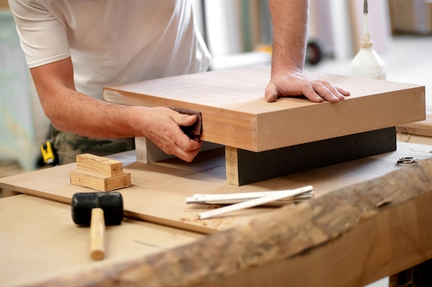 Carpenter sanding a wooden block manually