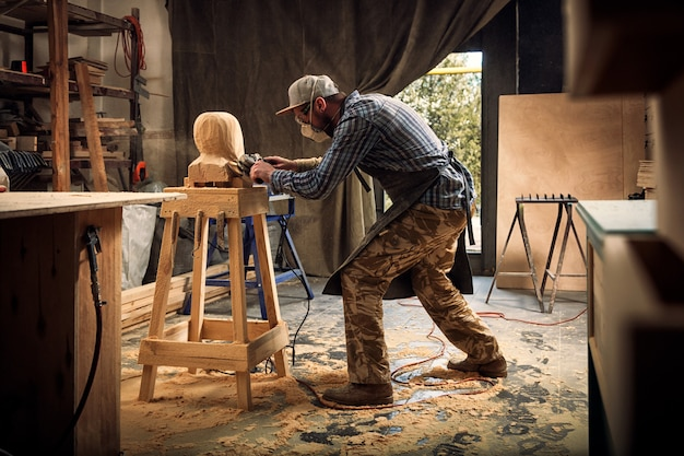 Carpenter  saw to cut out sculpture from wooden a man's head