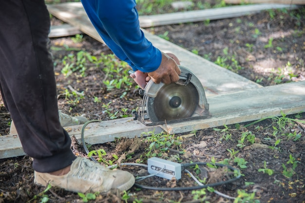 Плотник пилит доску, столярные стружки от дисковой пилы на строительной площадке