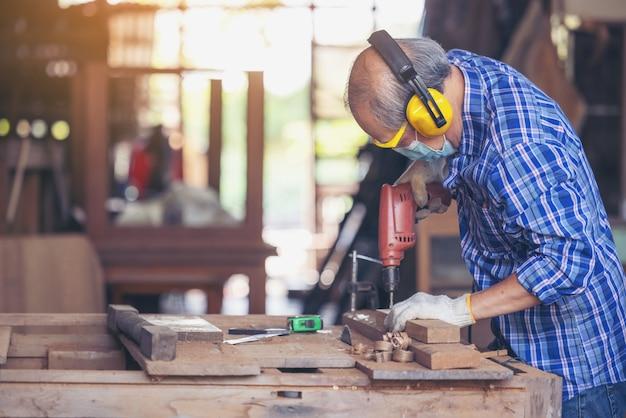 Плотник, старший мужчина, шлифовальный деревянный забор на рабочем месте с помощью рабочего инструмента