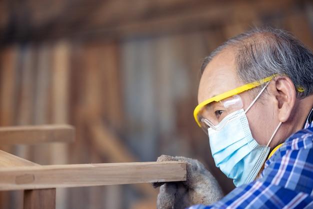 Carpenter, senior man sanding wooden fence in workplace using work tool