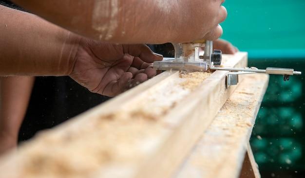 Плотник режет дерево в ремесленной мебели с помощью машины в мастерской
