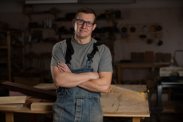 A carpenter stands with his arms crossed in his woodworking shop