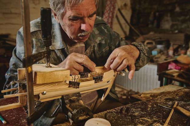 Плотник наклеивает деревянную деталь на деревянный корабль. мастер в мастерской делает деревянную игрушку, деревянную модель парусника.
