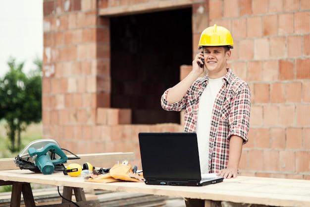 携帯電話で話している大工