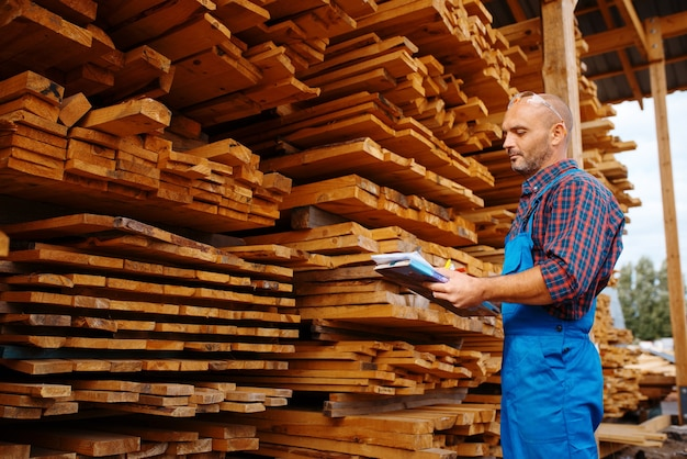 Carpenter in uniform check boards on sawmill, lumber industry, carpentry. wood processing on factory, forest sawing in lumberyard, warehouse outdoor