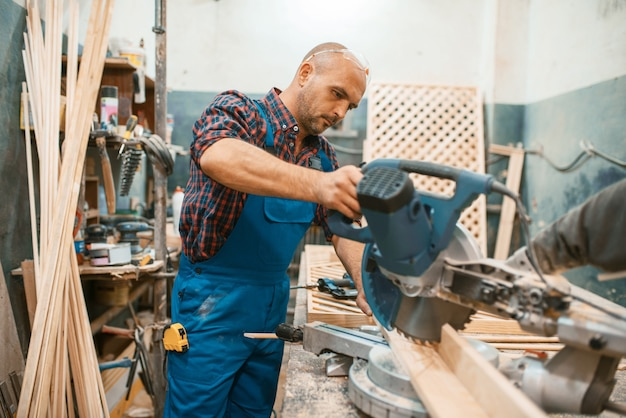 Carpenter in uniform works on circular saw, woodworking, lumber industry, carpentry. wood processing on furniture factory, production of products of natural materials