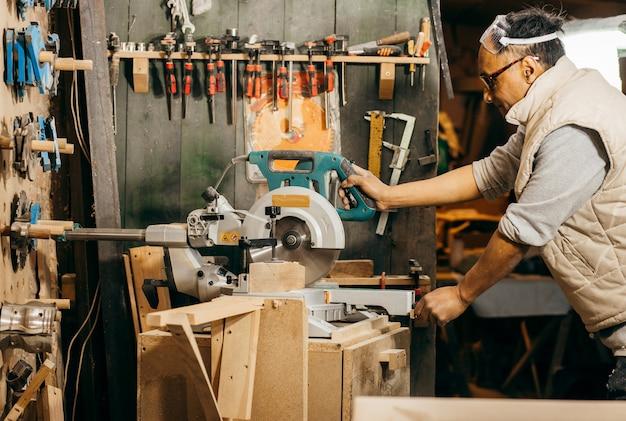 Плотник с помощью дисковой пилы обрезал длину деревянных стоек.