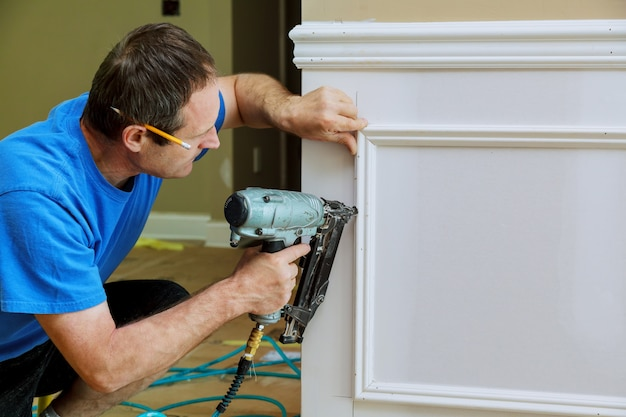 Carpenter using a brad nail gun to complete framing trim