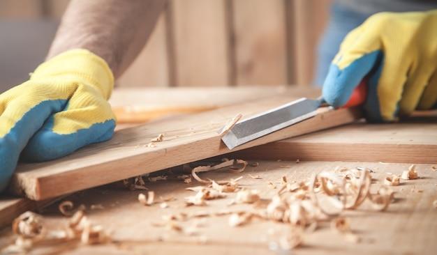 木の板にノミを使用する大工