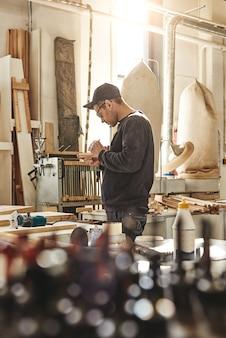 Плотник с помощью долота для резьбы по дереву в мастерской