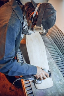 Carpenter using circular saw for cutting wooden boards. construction details of male worker or handy man with power tools Free Photo