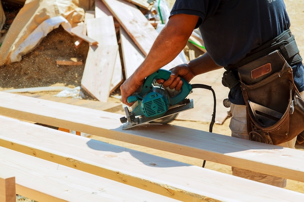 Carpenter using circular saw for cutting wooden boards. construction details of male worker