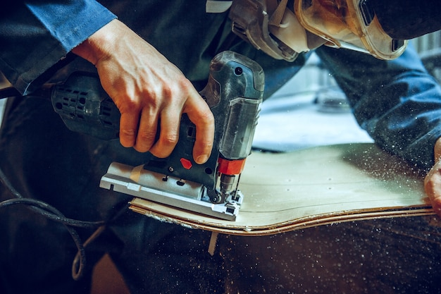 Carpenter using circular saw for cutting wooden boards
