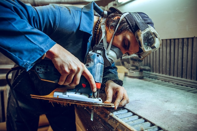 Плотник использует циркулярную пилу для резки деревянных досок. строительные детали мужского рабочего или умелого человека с электроинструментами