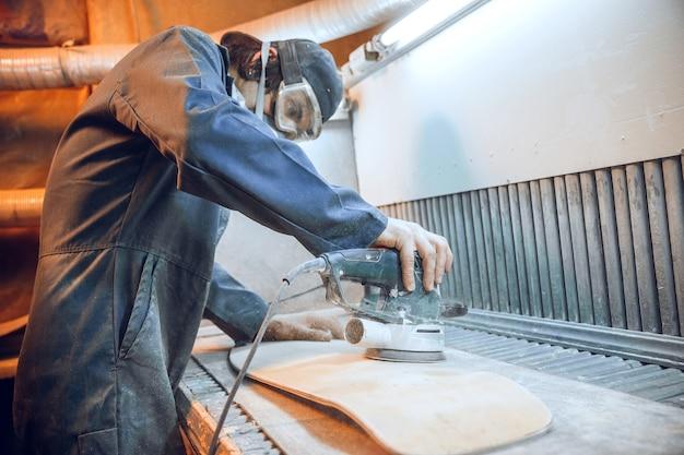 木の板を切るために丸鋸を使用する大工。電動工具を持った男性労働者または便利屋の構造の詳細