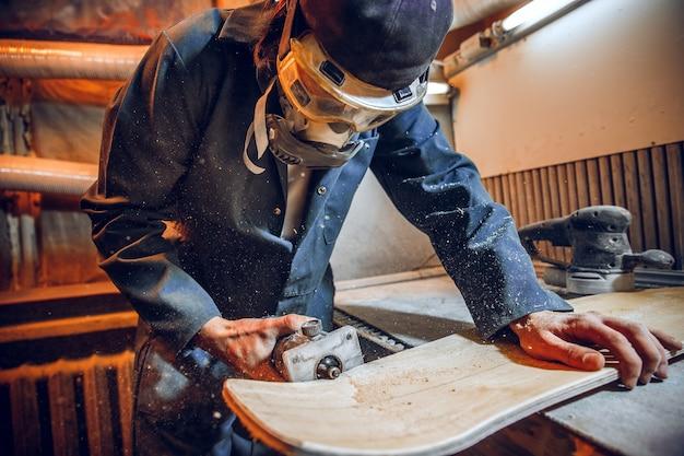 木の板を切るために丸鋸を使用する大工。電動工具を持った男性労働者または便利な男性の構造の詳細