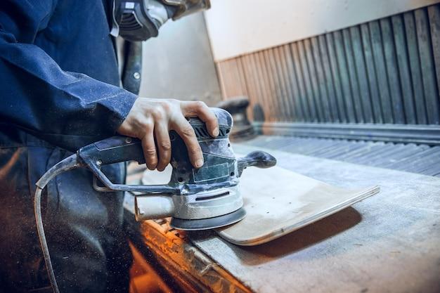목수는 나무 판을 절단하기 위해 원형 톱을 사용합니다. 남성 노동자 또는 전동 공구를 가진 잡역부의 건설 세부 사항