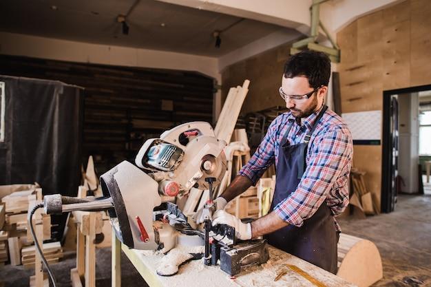 大工は彼のワークショップで木材に丸鋸を使用して