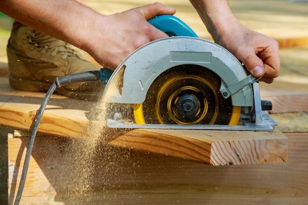목재 빔에 원형 톱을 사용하는 목수 새로운 주택 건설 프로젝트