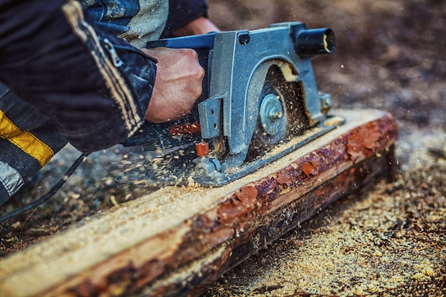 Carpenter using circular saw for wood. close-up