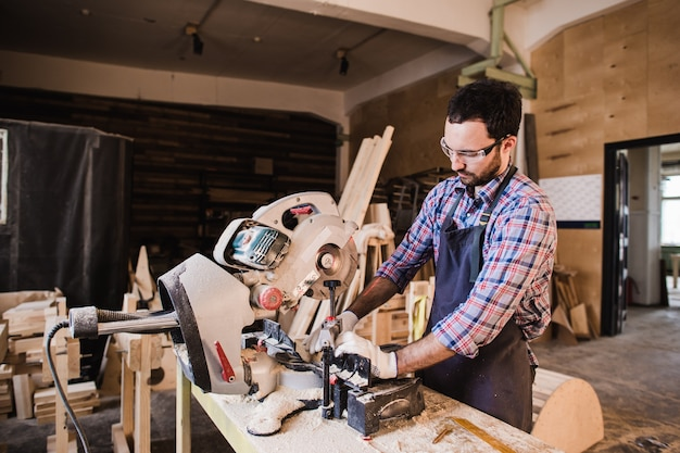 Carpenter using circular saw for wood at his workshop