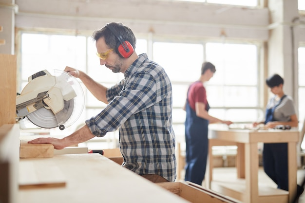 Carpenter using disksaw at factory