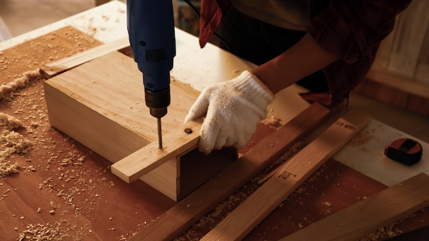 Carpenter using drill to screwing pieces of board at site.