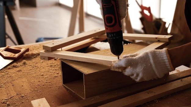 大工はドリルを使用して現場でボードの破片をねじ込みます。