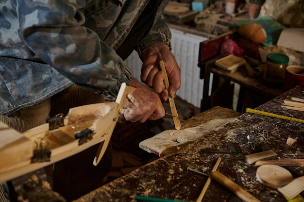 Плотник с помощью инструментов вырезал часть деревянного материала, чтобы сделать деревянную модель парусника. изготовление деревянных игрушек ручной работы. крупный план. мастер в действии