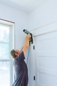 Carpenter using nail gun to moldings on door, framing trim,