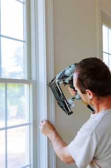 Carpenter using nail gun to moldings on windows, framing trim,