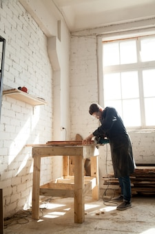Carpenter using power hand saw cutting wooden planks in workshop