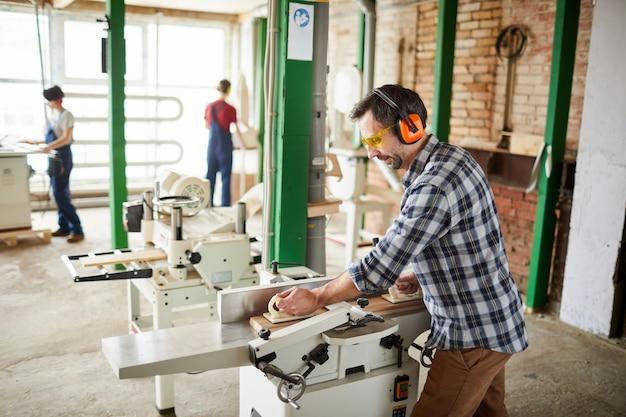 Плотник, используя деревообрабатывающие станки в мастерской