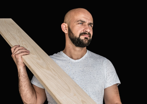 A carpenter in a white t-shirt with an ash-tree board at the ready. looking away. on a black background. isolate
