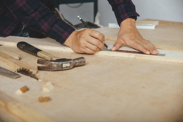 Плотник с меткой карандаша и правителя на деревянной доске на таблице. строительная индустрия, работа по дому сделай сам.