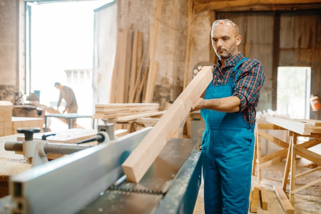 Carpenter with board near plane machine, woodworking, lumber industry, carpentry. wood processing on furniture factory, production of products of natural materials