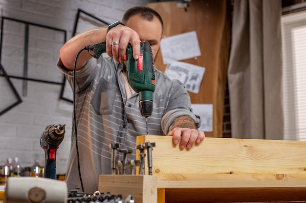 Carpenter with electric drill drilling wood plank at workshop