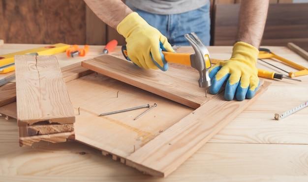 木の板に釘を打つハンマーで大工