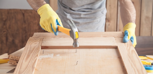 Carpenter with hammer hitting nail on wooden plank.