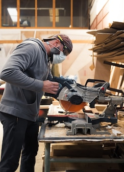 Carpenter with mask and protective glasses cutting a wooden slat with a circular saw