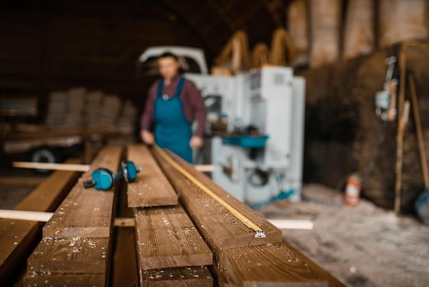 Плотник с рулеткой меряет доски, деревообрабатывающий станок, деревообрабатывающая промышленность, столярные изделия. обработка древесины на заводе, распиловка леса на складе